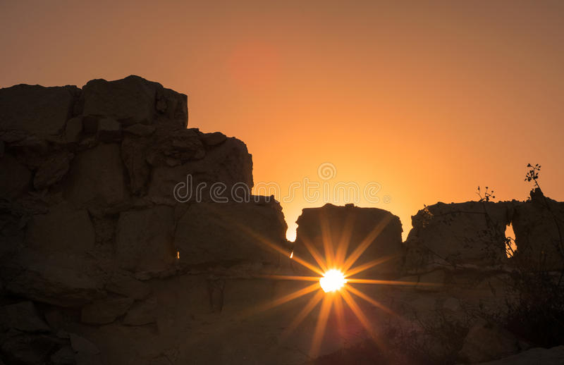 Sunset. Beautiful sun lights through the stone wall stock photo