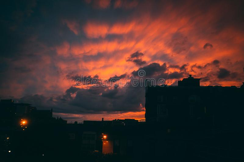 Sunset behind buildings with red light. Red sunset behind buildings in urban environment with gorgeous rays behind clouds royalty free stock photography
