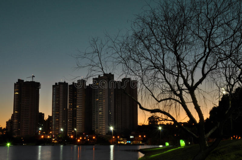 Sunset behind the buildings, water reflecting the lights and the beautiful silhoue royalty free stock photo