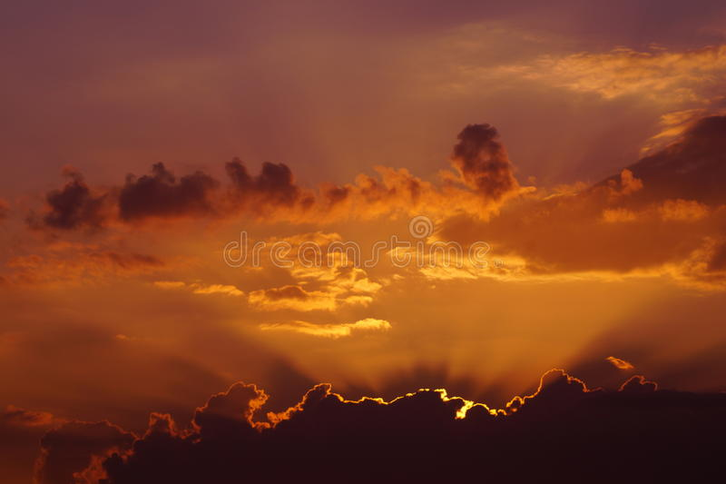 Sunset behind clouds stock photos