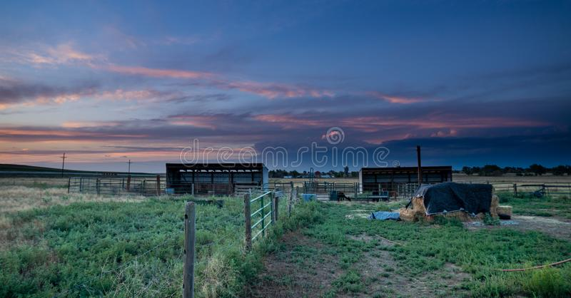 Sunset behind fencing in Eastern Plains Colorado. A pink and purple sunset behind metal panel fencing, barns and fields in eastern plains Colorado stock images
