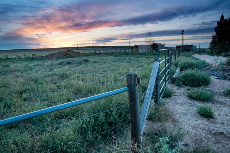Sunset behind fencing in Eastern Plains Colorado. A pink and purple sunset behind metal panel fencing, barns and fields in eastern plains Colorado royalty free stock photo