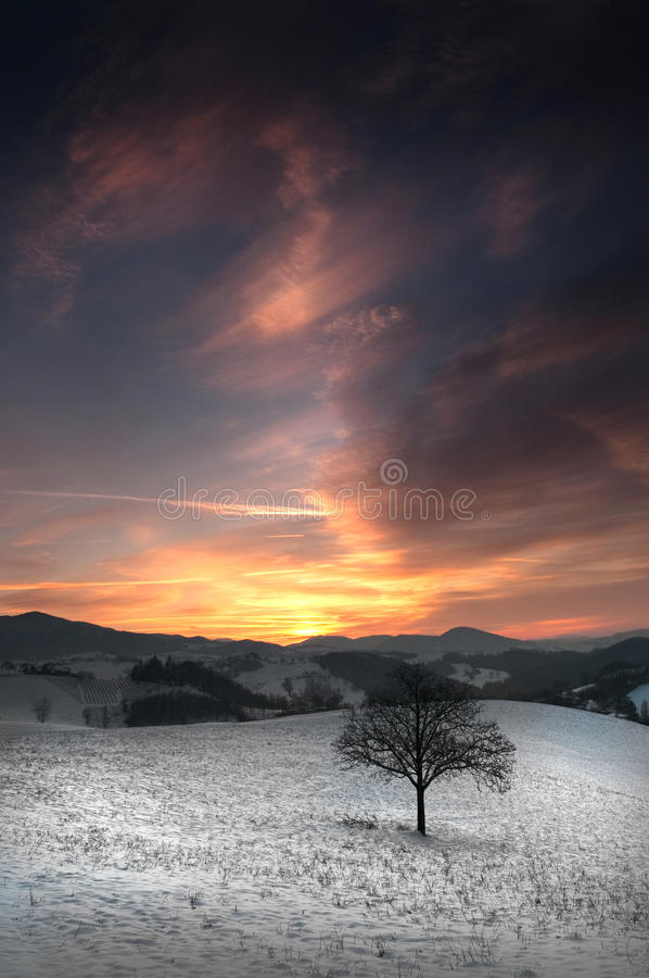Sunset behind the hills. Covered by snow stock photo