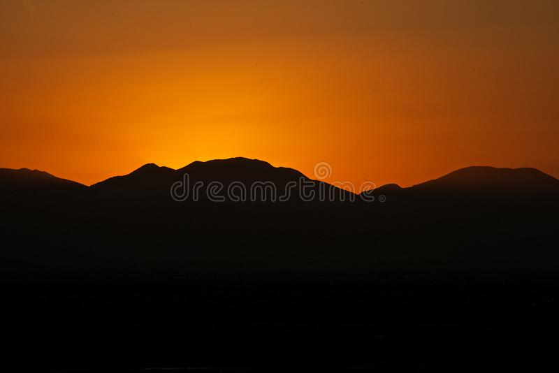 Close up of a red sunset behind the mountains royalty free stock photography