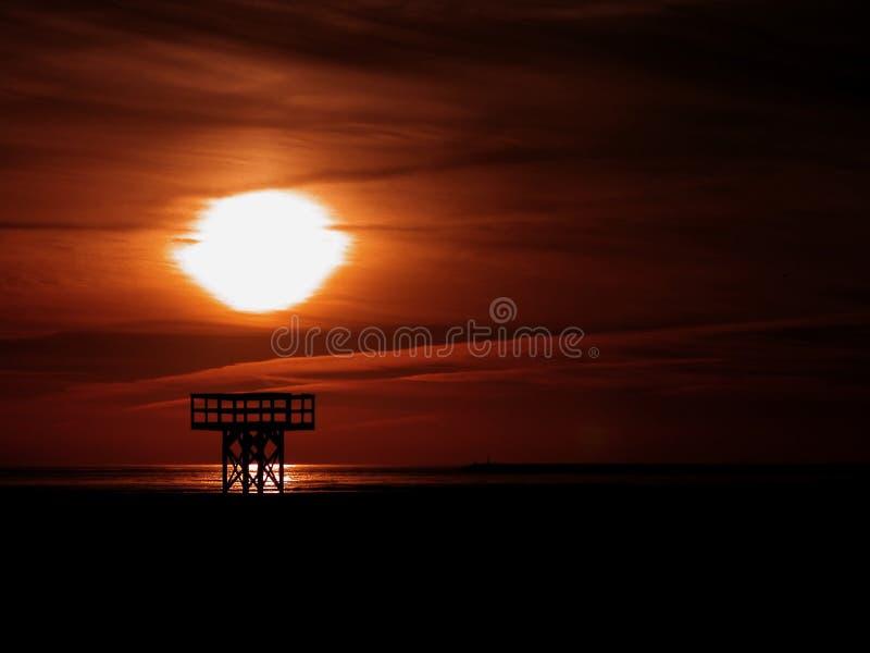 Sunset behind an old beach wood platform royalty free stock image