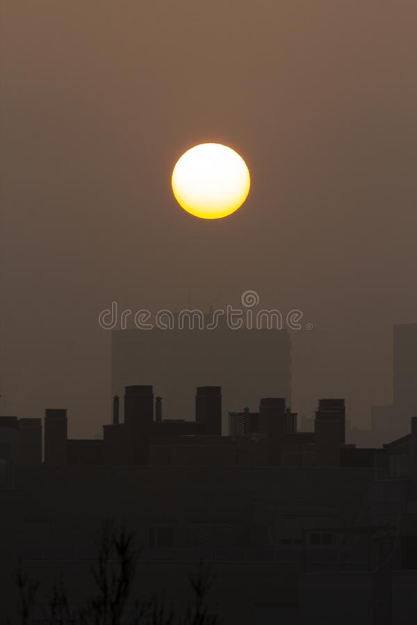 Sunset with a big round sun on a city with fog. Brown and orange colours royalty free stock image