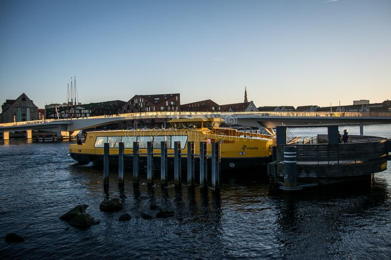 Public ferry and a bike bridge behind in Copenhagen Harbor. Denmark. Sunset in the bike bridge behind. Public ferry in the front in Copenhagen harbor. Very royalty free stock images