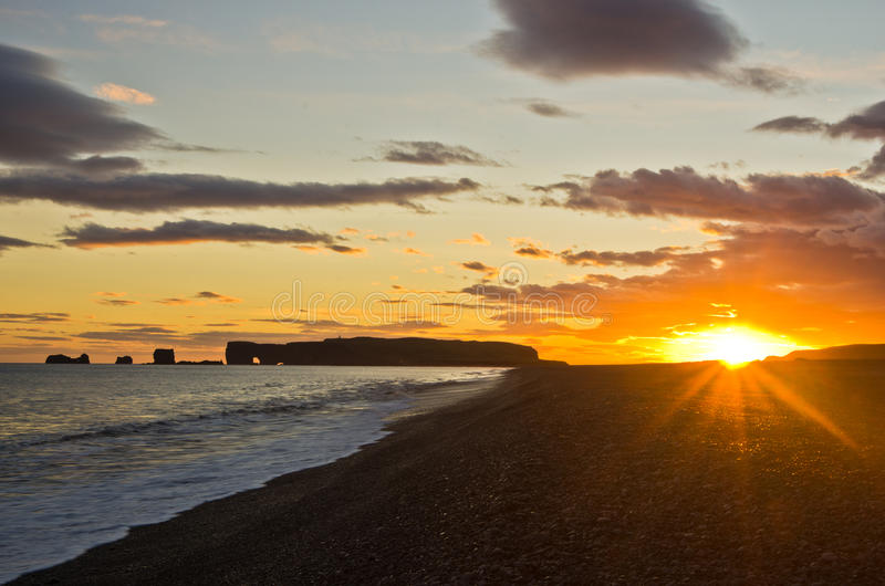 Sunset on black beach with Dyrholaey rock in background,Iceland. Sunset on a black beach near Vik with Dyrholaey rock in background, south Iceland royalty free stock photos