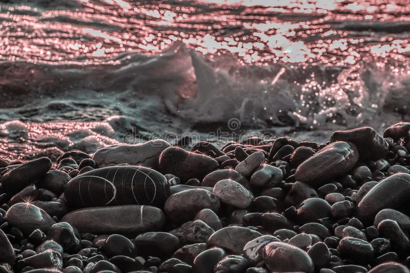 Sunset in the black sea. Sea pebbles. wet stone. beautiful background. sea water. game of colors royalty free stock photography