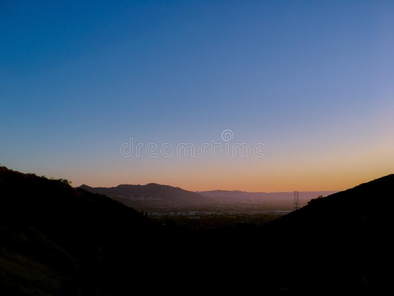 Sunset, blue sky. Dusk. Low Haze of the sun. Blue sky above. Colorful sky. sunset brightens the earth below the horizon. Sun setting from the side. Out of frame royalty free stock photos