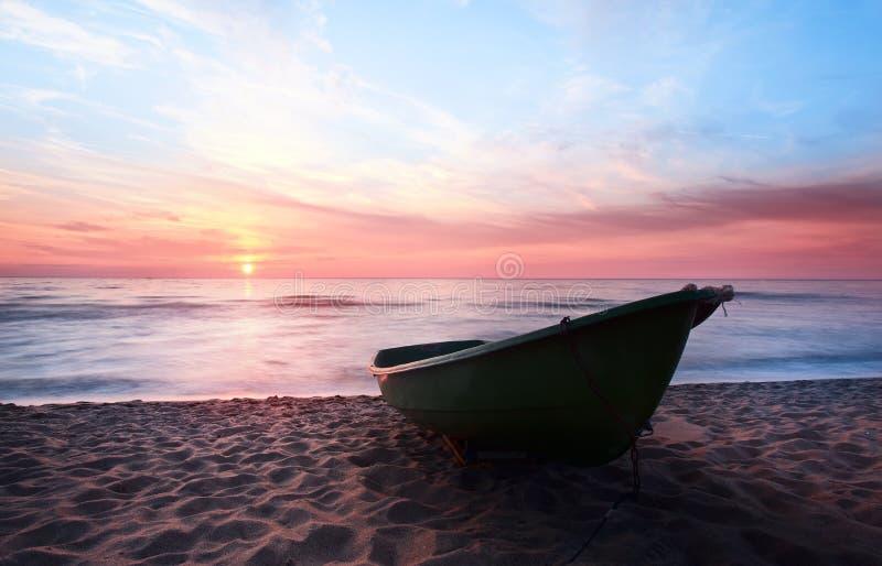 Sunset.Boat på kust. royaltyfri bild