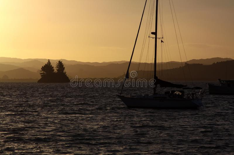 Sunset boat. Left small sailboat lays anchor in bay at beautiful sunset stock images