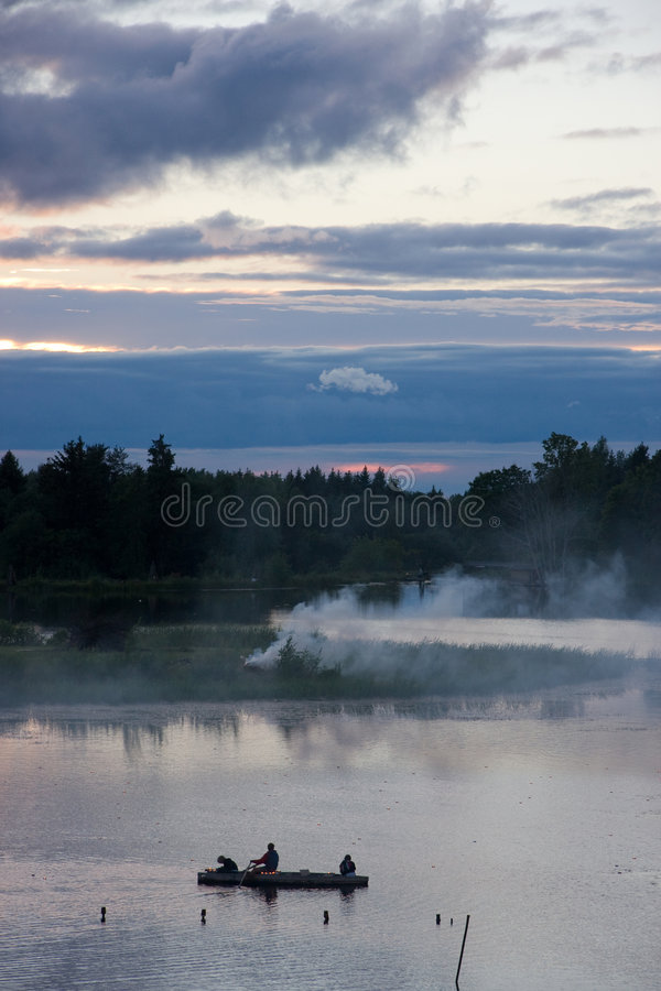 Sunset, boat and smoke royalty free stock photography