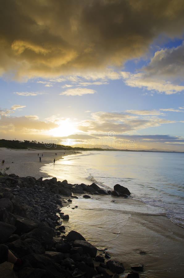 Sunset at Byron Bay Australia. Sunset as surfers, beach walkers and holidaymakers end the day at Belongil Beach, Byron Bay in New South Wales, Australia. Iconic stock images