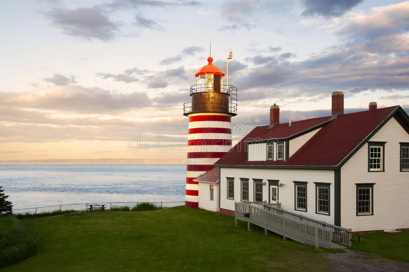 """Sunset by Candy Cane Lighthouse in New England. Sunset by West Quoddy Head lighthouse, with its red and white stripes, referred to as the """"candy cane stock photos"""