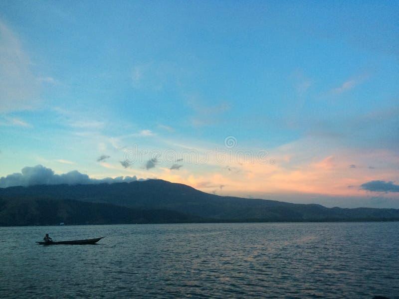 Sunset. Canoe at Sentani Lake, Papua royalty free stock photography