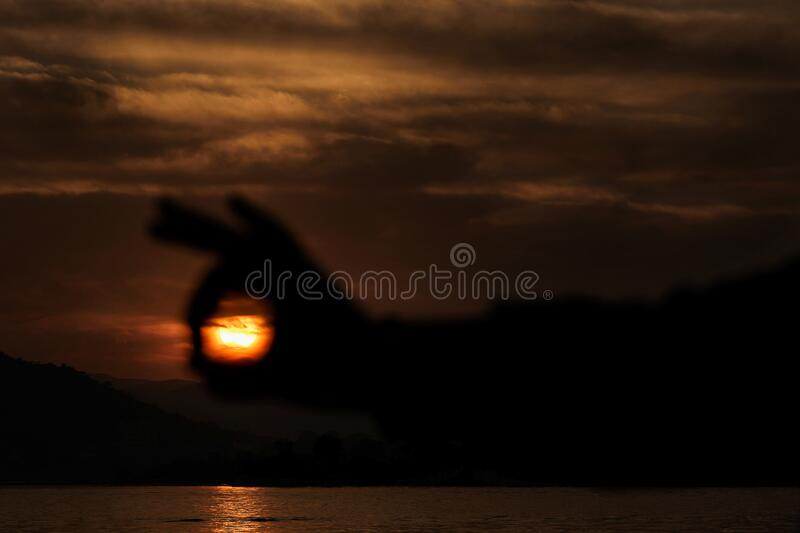 Sunset captured within the hands. Landscape photograph of a Sunset captured within the silhouette of a man`s hand royalty free stock photos