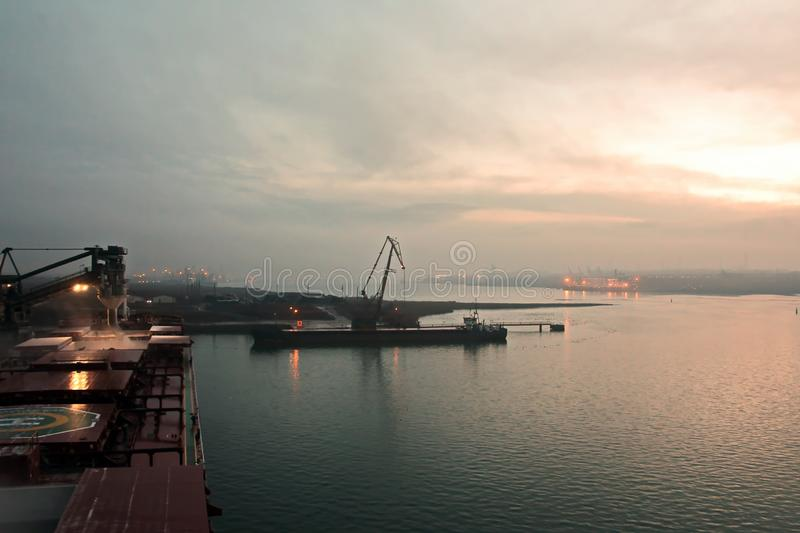 Sunset.Cargo terminal for loading grain cargo and containers with coastal cranes. Port Yuzhny, Ukraine. January, 2019 royalty free stock photos