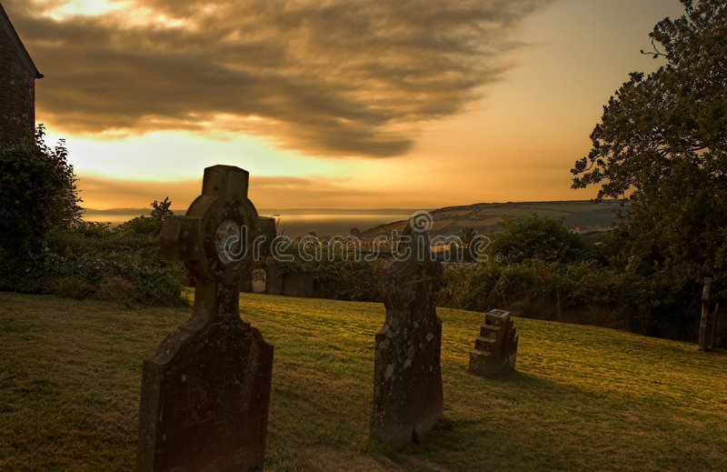 Sunset church yard. Church yard at sunset in Wales, with view on the beach royalty free stock image
