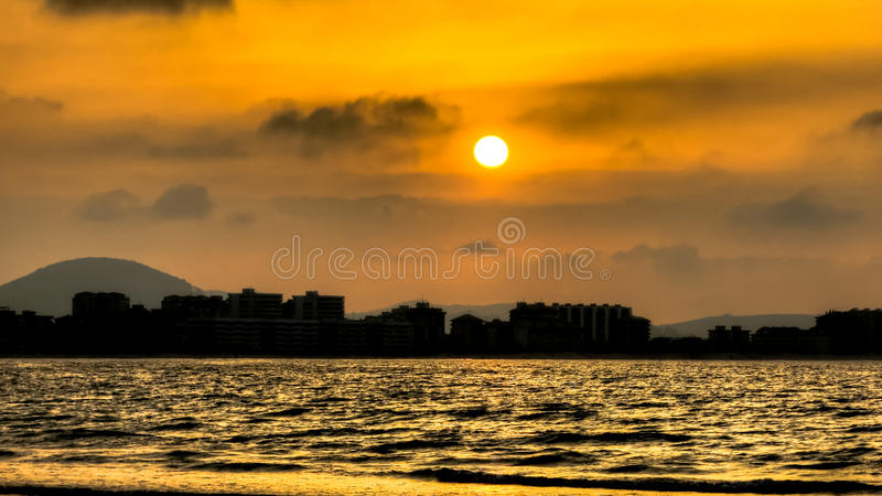 The sunset at the city and ocean. royalty free stock images