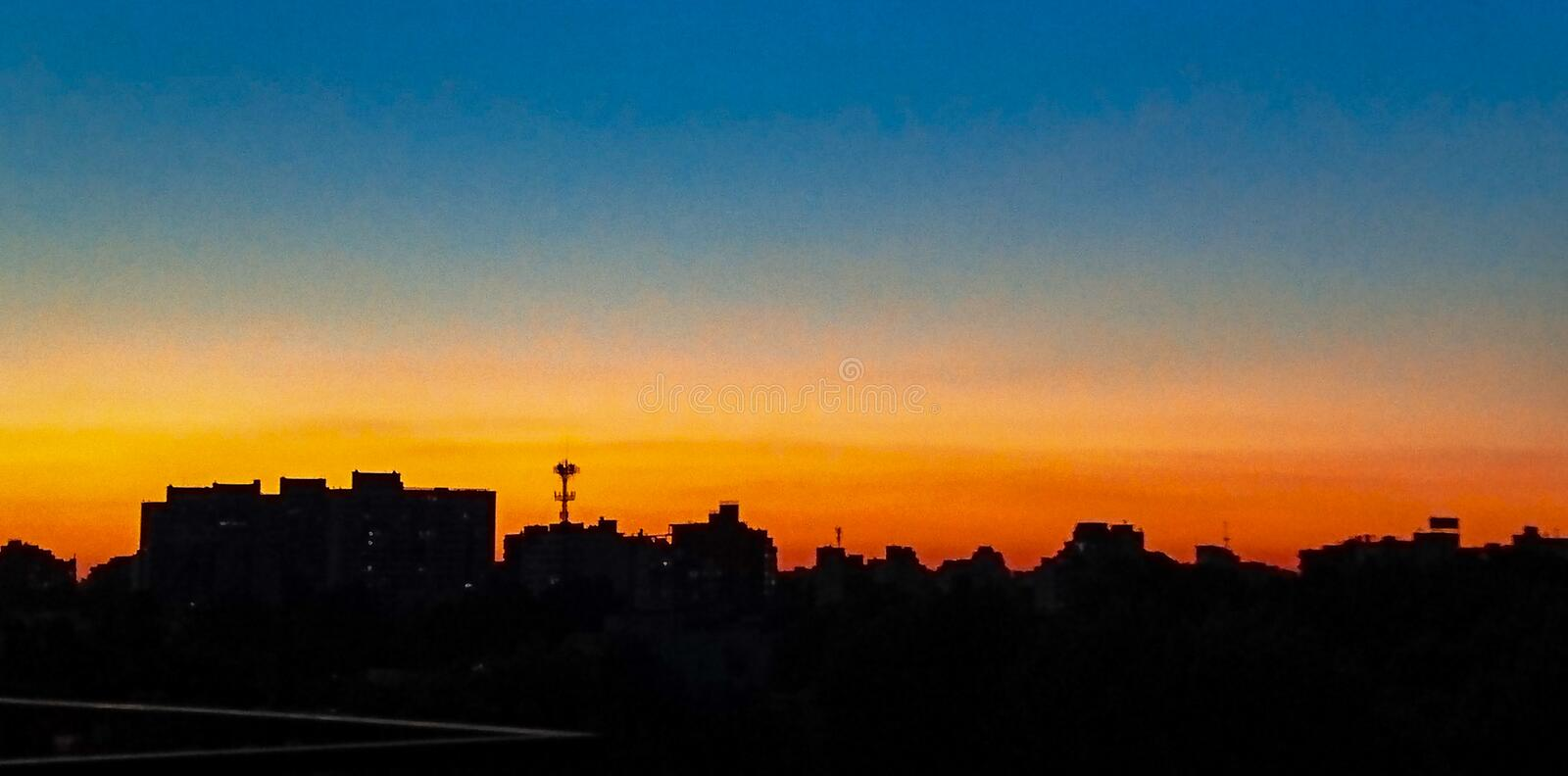 Sunset in the city orange and blue hour sky stock image