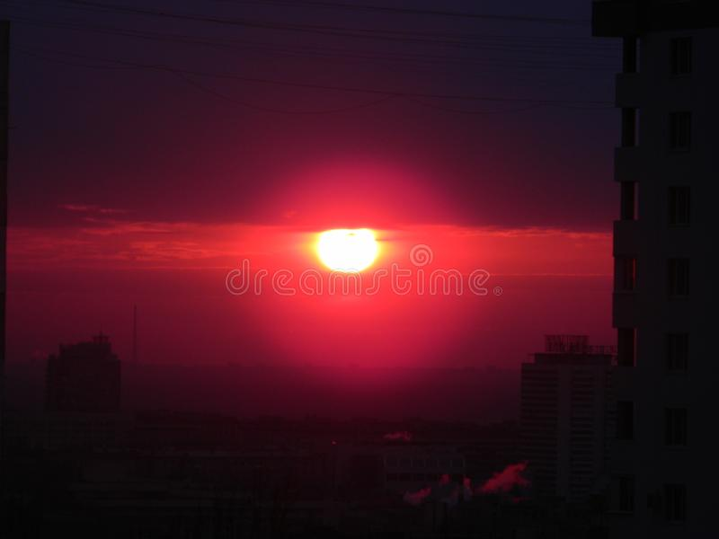 Sunset in the city. When the sun touches the horizon, the evening twilight begins. And with its fireball it colored one city in dark red. And the clouds in the royalty free stock photography
