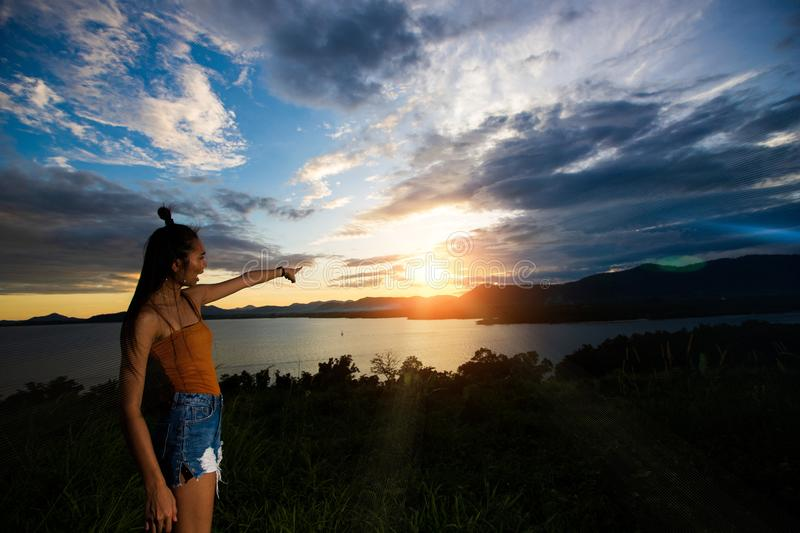 Sunset cloud beam to young adult asian woma stock photography