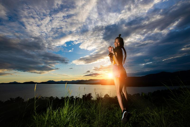 Sunset cloud beam to young adult asian woma royalty free stock photography