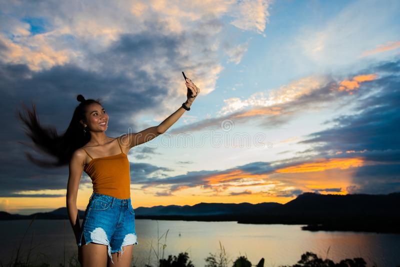 Sunset cloud beam to young adult asian woma royalty free stock images