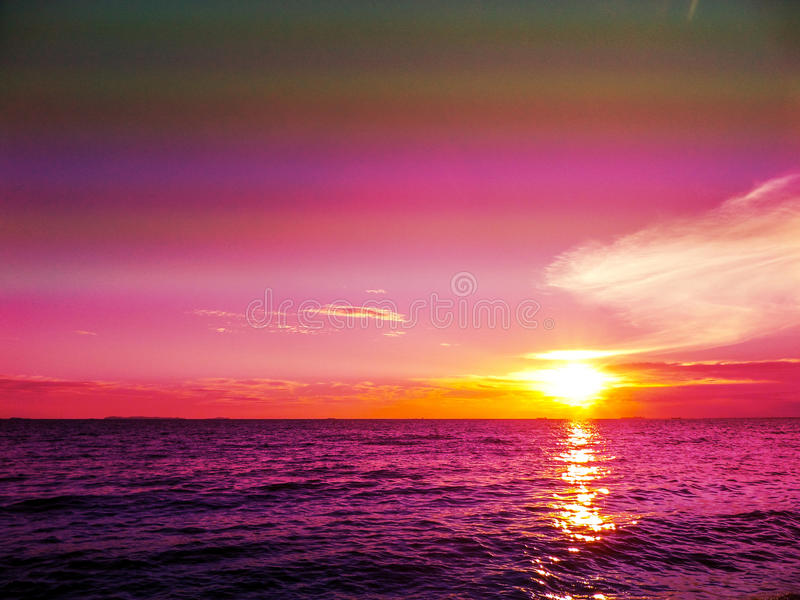 Sunset and cloud on horizon and dark purple water royalty free stock image