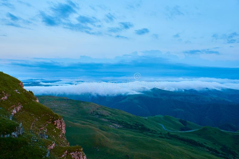 Sunset clouds, blue sky and fog over a mountain green valley with a village and a winding road. Sunset clouds, blue sky and fog over a mountain valley with a stock photo