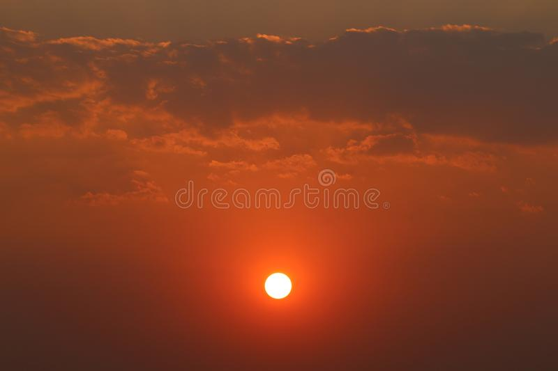 Sunset. A sunset with clouds hovering over the sun and orange tinged sky stock photos