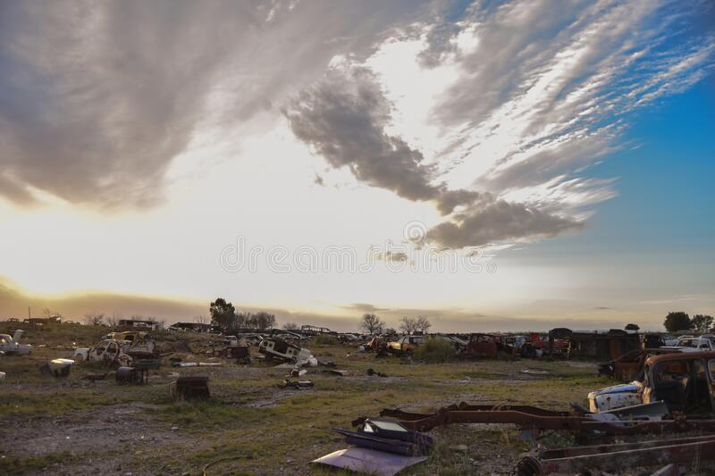 Sunset with clouds in old car depot. Junkyard. Rusty cars stock image