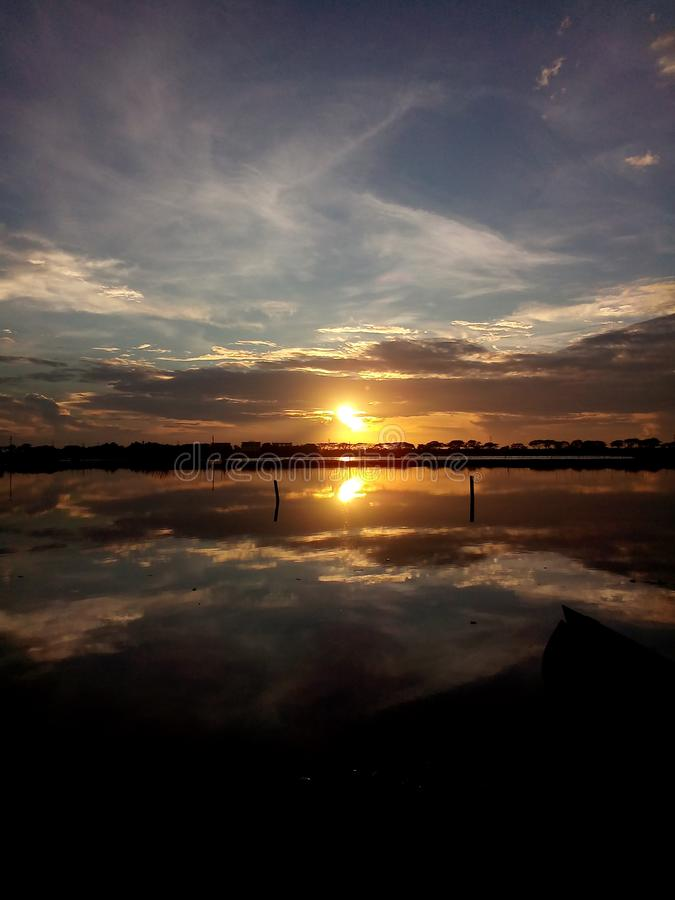 Sunset on cloudy blue sky with water reflections, Landscape royalty free stock photo