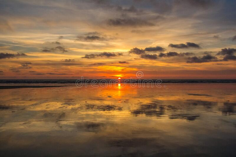 Sunset in cloudy skies over water royalty free stock images