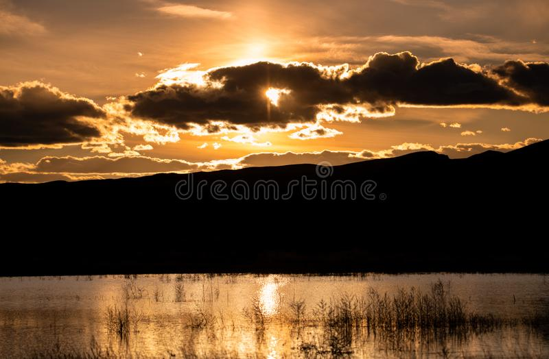 Sunset with a cloudy sky at Bosque del Apache, New Mexico. At the pond royalty free stock photography