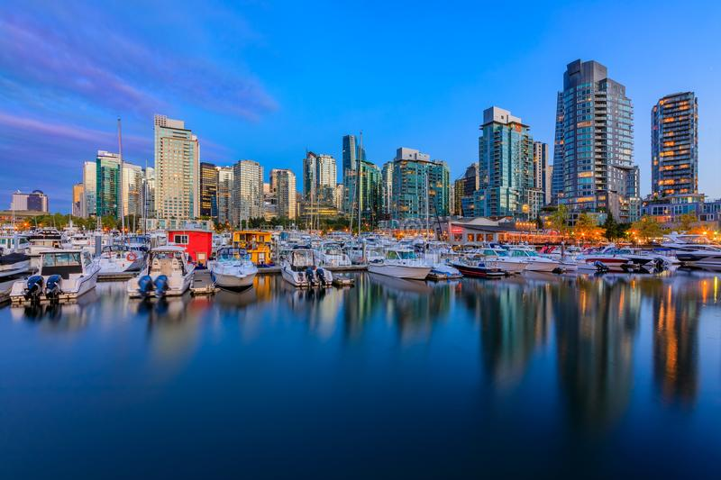 Sunset at Coal Harbour in Vancouver British Columbia with downtown buildings boats and reflections in the water. August 04, 2018 - Vancouver, Canada: Sunset at royalty free stock photos