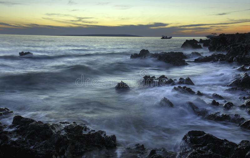 Sunset Coastline with Rocks and Ground Rush. Waves Crashing to Shore in Croatian Rocky Coastline in Sunset with Boats in Distance royalty free stock photo