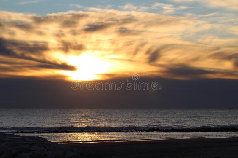 Sunset on a cold day at the beach. This photo is made at the beach in Marina di Massa in Italy. It was a cold windy day. The sun was behind the dark clouds. But stock photo