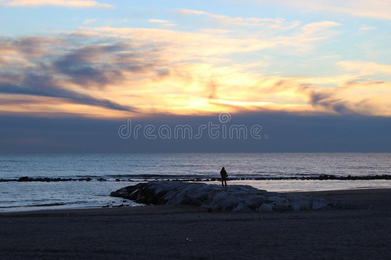 Sunset on a cold day at the beach. This photo is made at the beach in Marina di Massa in Italy. It was a cold windy day. The sun was behind the dark clouds. But royalty free stock photo