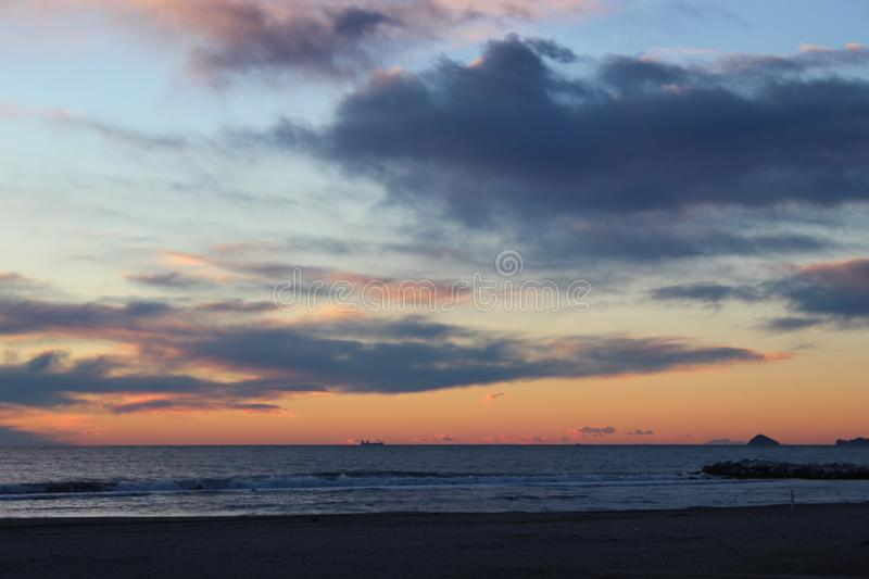 Sunset on a cold day at the beach. This photo is made at the beach in Marina di Massa in Italy. It was a cold windy day. The sun was behind the dark clouds. But stock photos