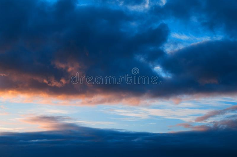 Sunset colorful sky background - pink, orange and blue dramatic colorful clouds lit by evening sunshine. Sunset colorful sky background - blue dramatic colorful stock photo