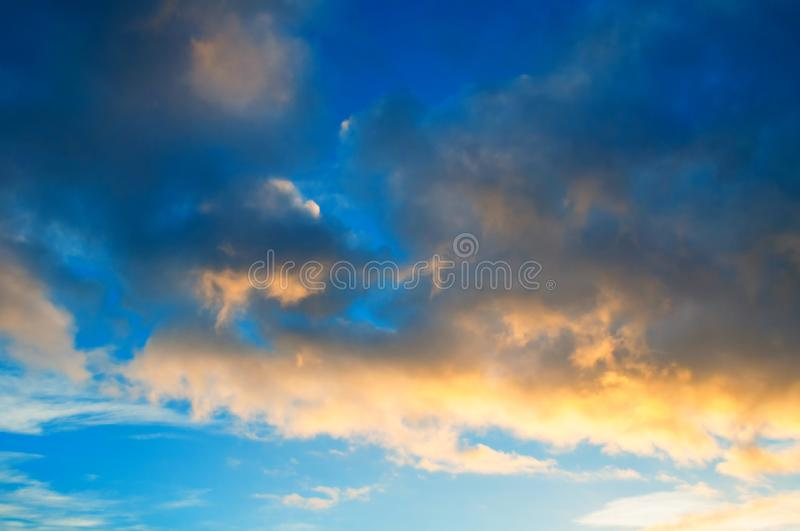 Sunset colorful sky background - orange and blue dramatic colorful clouds lit by evening sunshine. Sunset colorful sky background - pink, orange and blue stock photography