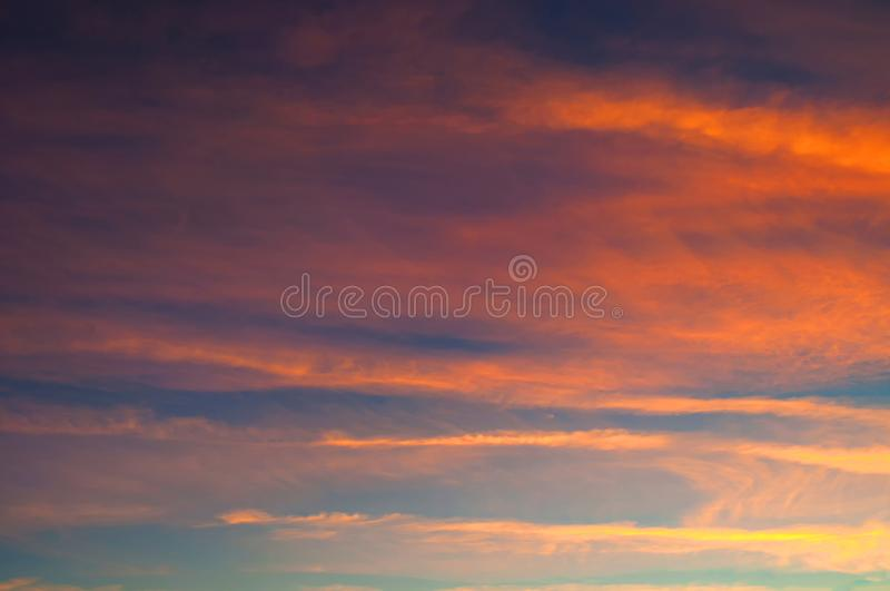 Sunset colorful sky background - pink, orange and blue dramatic colorful clouds lit by evening sunshine. Vast sunset sky. Landscape royalty free stock photography