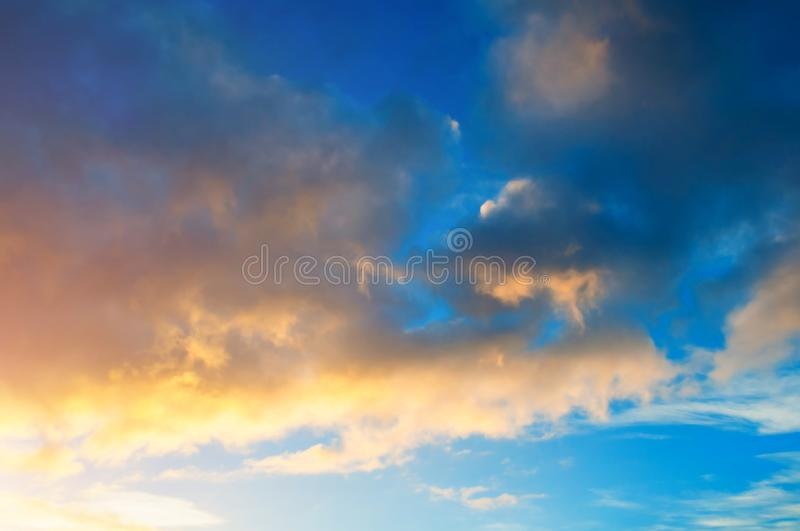 Sunset colorful sky background - pink, orange and blue dramatic colorful clouds lit by evening sunshine. Vast sunset sky landscape royalty free stock photography