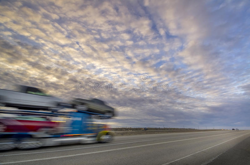 Sunset colors over interstart with eighteen wheeler. Long haul truck driver rides into the sunset royalty free stock photos