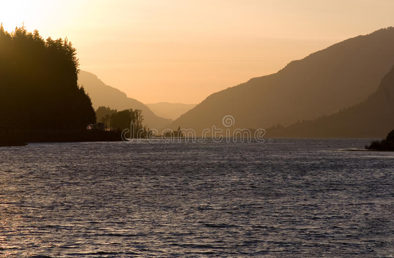 Sunset in the Columbia River Gorge. A train runs up the Columbia River Gorge at Sunset stock photos