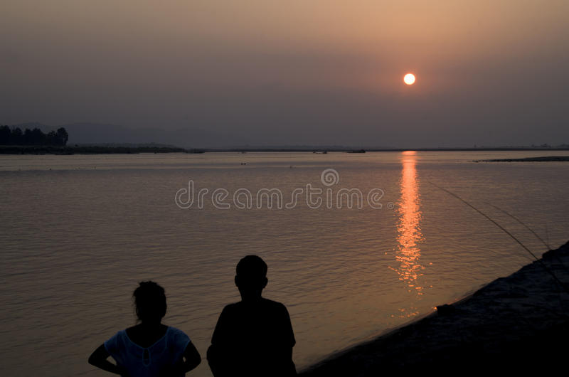 Sunset Couple. A couple watching the sunset at Narayani River, Nepal royalty free stock photography
