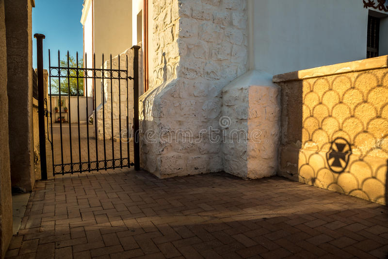 Sunset Cross at a Spanish Mission. The setting sun casts a moody shadow of a cross and ironwork on an adobe wall at an historic Spanish mission royalty free stock photo