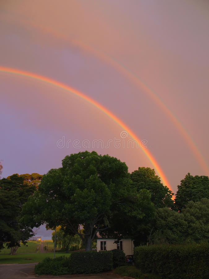 Sunset and double rainbows. Twin rainbows were formed on farmland royalty free stock photo